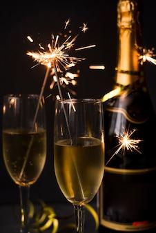 Крупный план шампанского и бенгальского огня на черном фоне