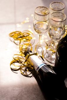 Крупный план пустой бутылки шампанского и бокал с золотыми лентами на вечеринке