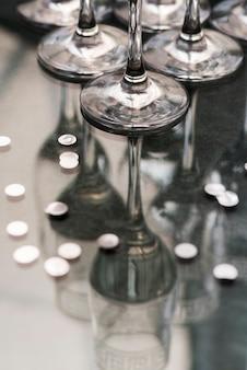 Прозрачные очки и серебряное конфетти над отражающим столом