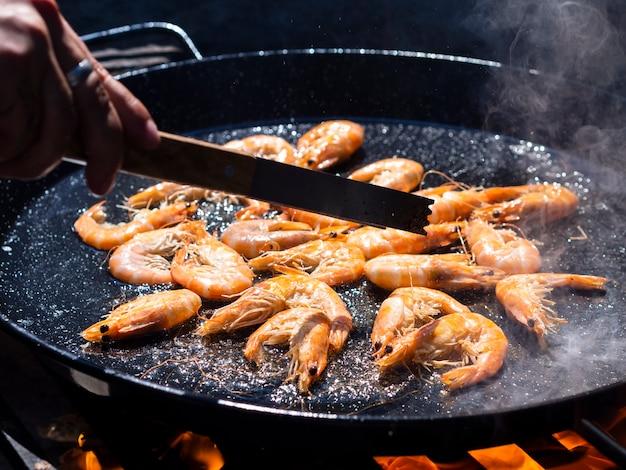 フライパンで油で揚げるエビ