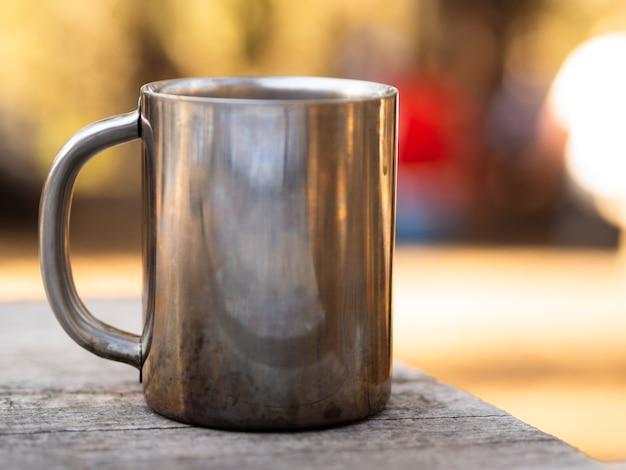ぼろぼろの木製テーブルにまぶしさと金属製マグカップ