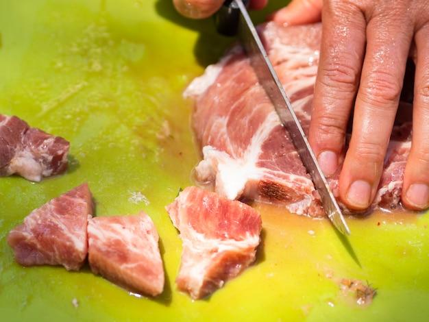 スライスボードに肉を切るシェフ