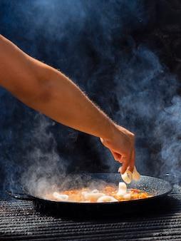 Кук, добавляющий кольца кальмаров к овощам на сковороде