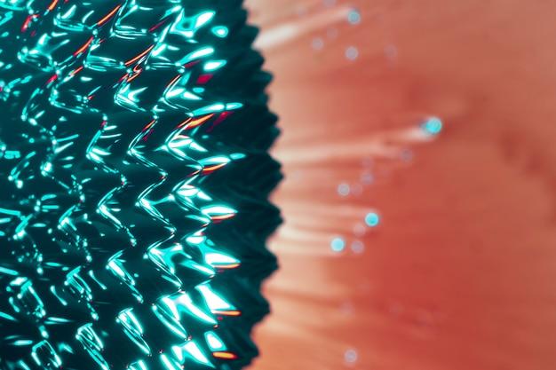 サーモン色の背景上の強磁性流体の抽象的なナノ粒子