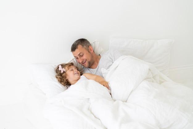 寝室で娘と一緒に座っている父