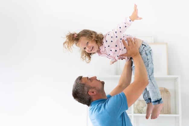 Вид сбоку отец держит дочь