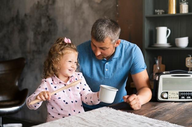 ミディアムショットの父と娘、台所