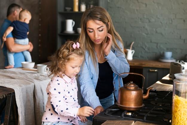 ミディアムショットの母娘と一緒にお茶を作る
