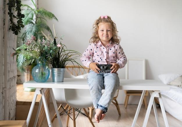 テーブルの上に座ってカメラを持つフルショットの女の子