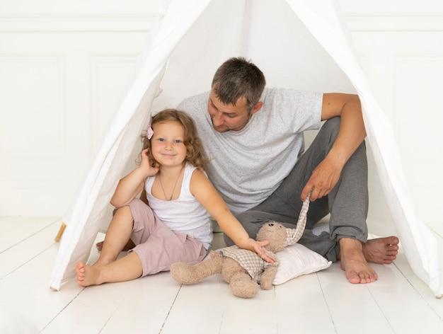 彼女のお父さんと座っているフルショット幸せな女の子