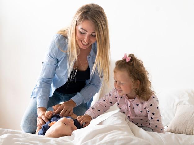 ミディアムショット幸せな母の子供たちと遊ぶ