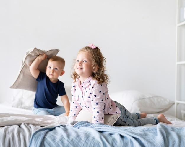 寝室に座っているフルショットの子供たち