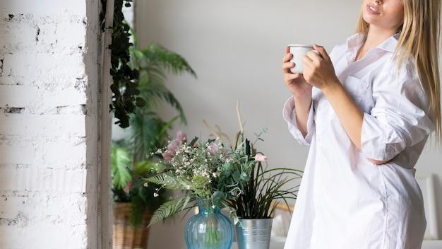 一杯のコーヒーとクローズアップのスマイリー女性