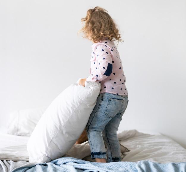 フルショットの女の子が枕と一緒にベッドで遊んで