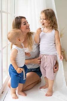 彼女の子供と一緒にいるフルショット幸せな母