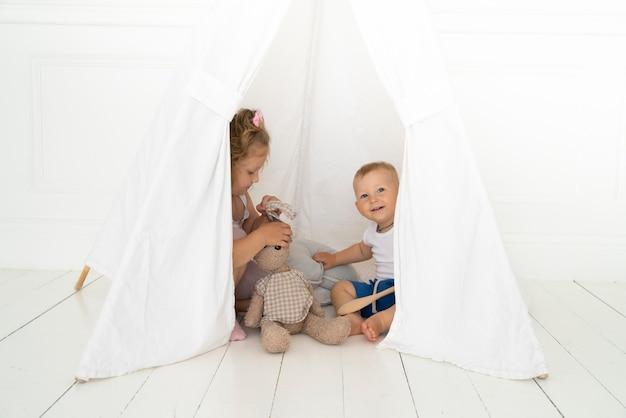 テントの下でフルショットの幸せな子供たち