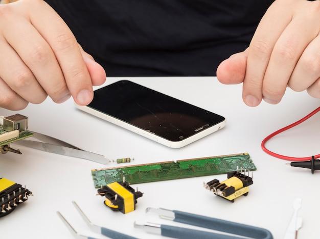 Человек сидит за рабочим столом с электроникой