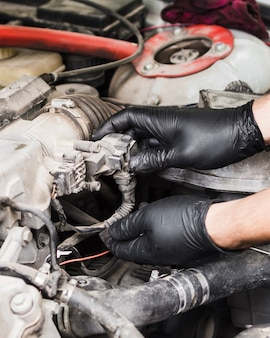 Человек делает ремонт двигателя автомобиля