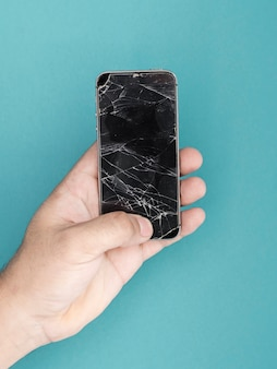 粉々になった画面で携帯電話を持って男