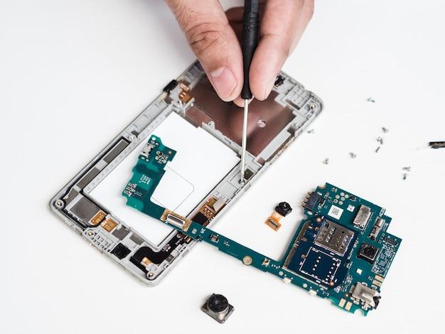 欠陥のある電話機を修理のために分解する