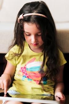 Крупным планом сидящая девушка смотрит на свой планшет