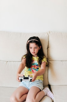 正面の女の子がビデオゲームをプレイ