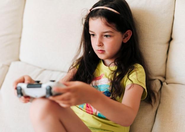 側面図の女の子がコントローラーでビデオゲームをプレイ