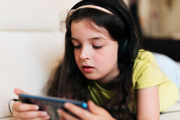 携帯電話を見てヘッドフォンでクローズアップの女の子