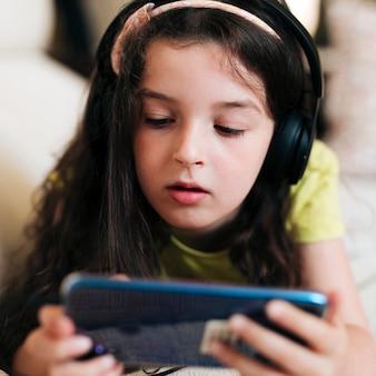 ヘッドフォンとスマートフォンのクローズアップの女の子