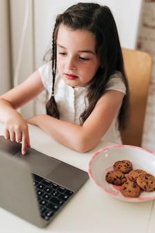 Девушка с печеньем смотрит на ноутбук