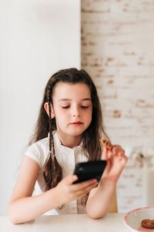 Средний снимок девушка с телефоном ест печенье