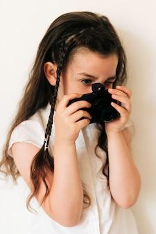 お下げと写真のカメラを持つ側面図少女
