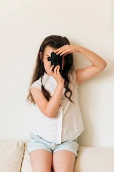ミディアムショットの女の子とお下げと写真のカメラ