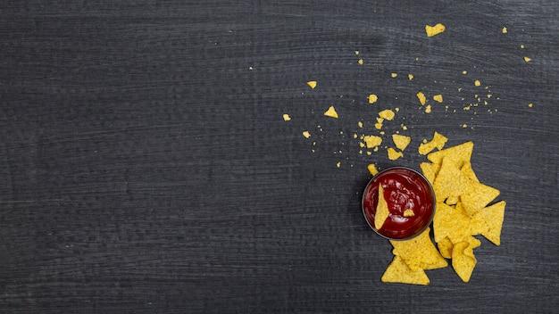 トマトのディップと砕いた伝統的なナチョス