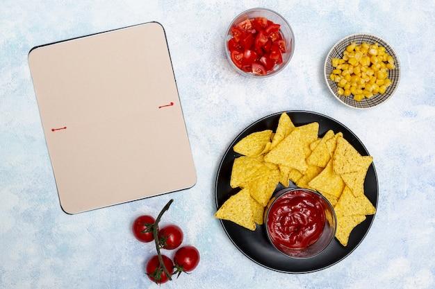 野菜のノートと黒のボウルにケチャップとナチョス