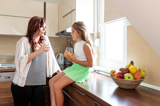 台所で母と娘のミディアムショット