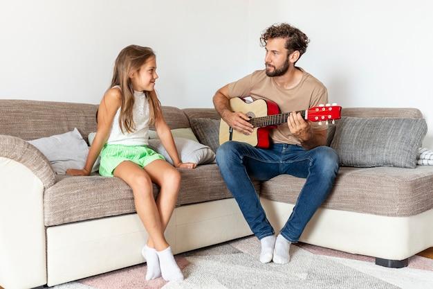 彼の娘のためにギターを弾く父
