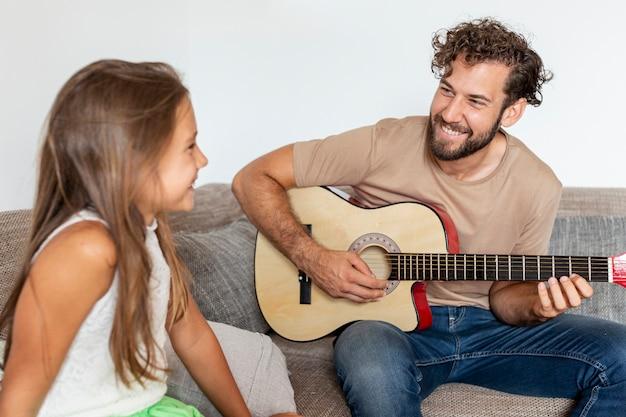 ギターを弾く父のミディアムショット