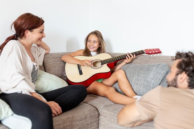 Маленькая девочка играет на гитаре для своих родителей