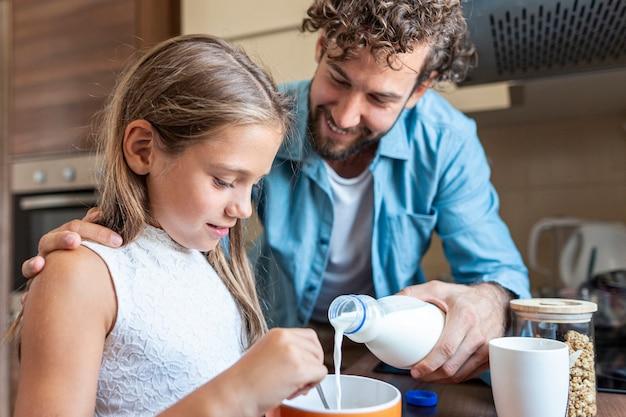 彼の娘のために牛乳を注ぐ父のミディアムショット