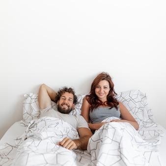 ベッドでリラックスしたカップルのミディアムショット