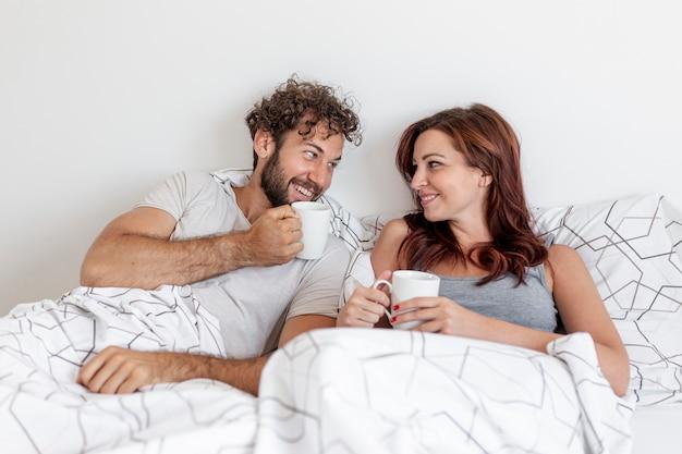かわいいカップルがベッドの中でコーヒーを飲む
