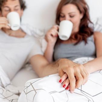 かわいいカップルがベッドでコーヒーを飲む背景をぼかした写真