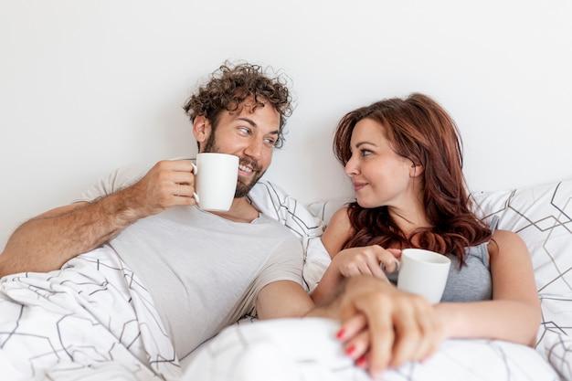 カップルはベッドの中でコーヒーを飲む