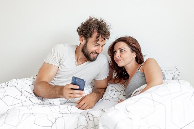 笑っているベッドの中でカップル