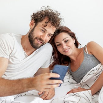 スマートフォンでベッドを見ているカップル