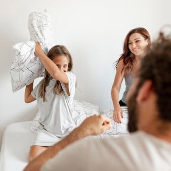 Красивая семейная подушка борется в постели