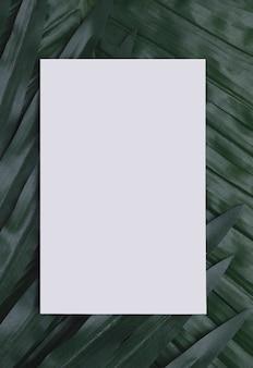 Белая бумага на тропических листьях копией пространства
