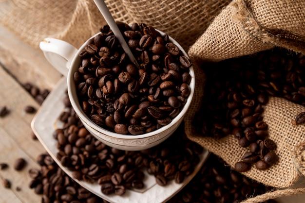 コーヒー豆のクローズアップでいっぱいのカップ