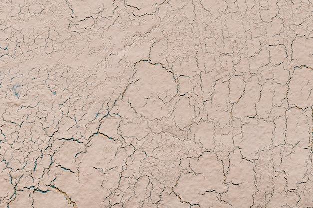 亀裂の背景を持つベージュライム石膏